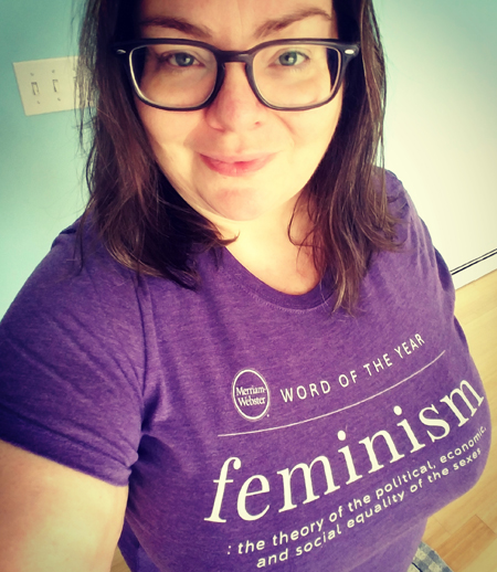 image of me from the waist up wearing a purple t-shirt with text from Merriam-Webster declaring 'feminism' the Word of the Year