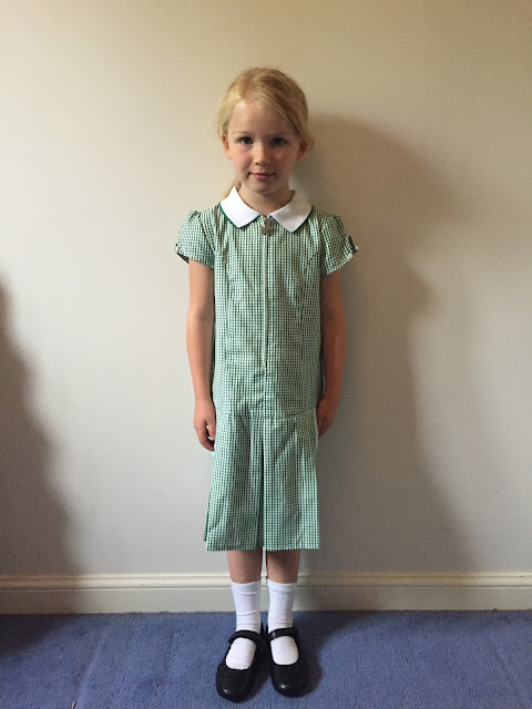 A little girl in a green and white summer dress on her first day of school