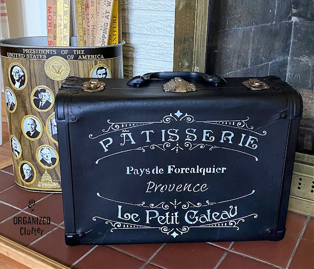 Photo of a vintage suitcase upcycled with black paint & a French stencil