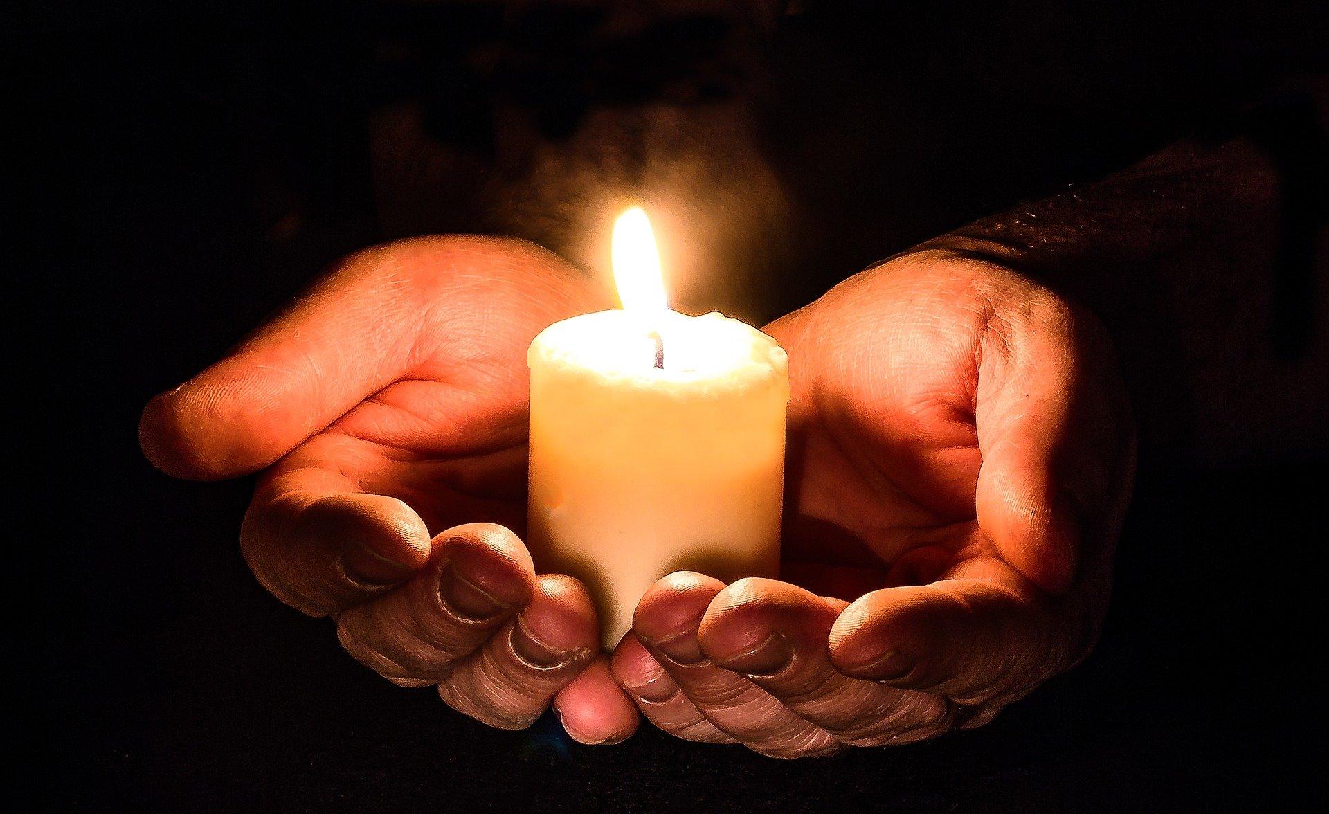 رجل يحمل شمعة بكلتا يديه