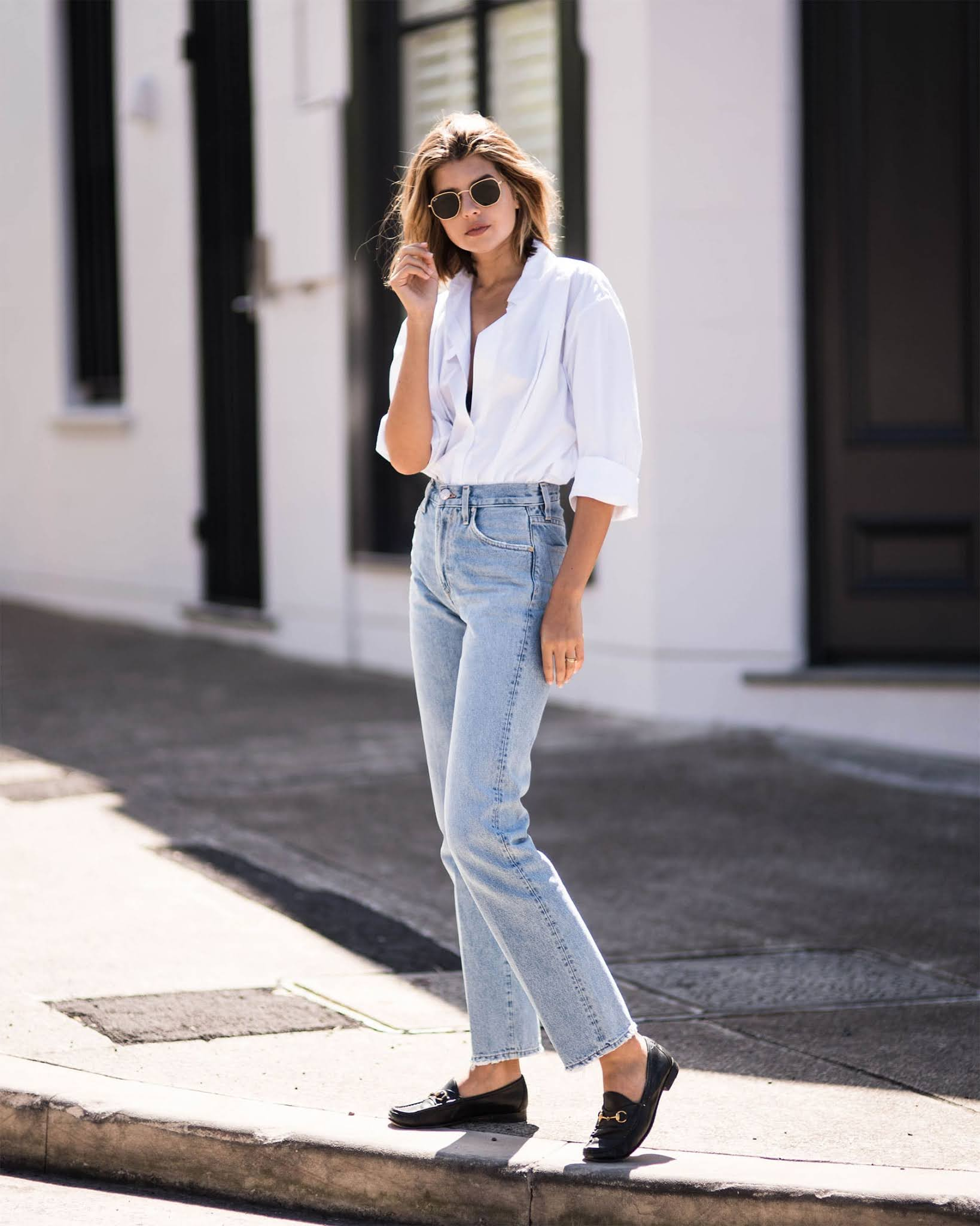 Under-$100 Casual Spring Outfit Idea — Tailsa Sutton in round sunglasses with metal frames, a crisp white button-down shirt, classic straight-leg jeans, and black loafers