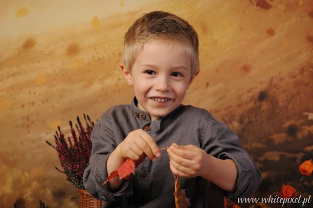Chłopiec na fotografii bawi się liśćmi
