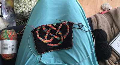 In progress colorwork knitting: black background, rainbow variegated knotwork. The two balls of yarn are on either side of the lap the knitting rests on