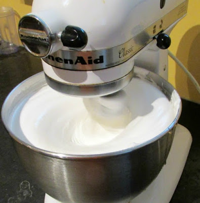 stand mixer running with bowl absolutely full of bright white fluffy frosting