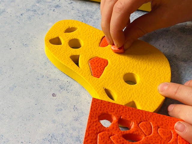 Close up photo of pushing a piece of orange foam into the larger yellow body piece to make giraffe print