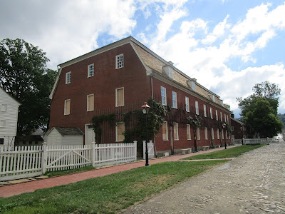 Large 3-story brick building set next to a cobblestone street and white picket fence. Some windows are boarded up due to a restoration project.