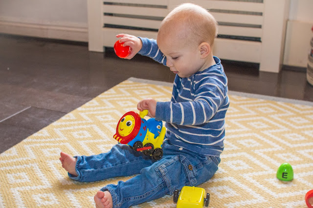baby playing with a plastic train and egg