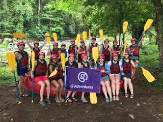 """Large group of women posing with their raft and paddles, holding sign that reads """"G Adventures"""""""
