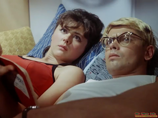Aleksandr Demyanenko and Natalya Seleznyova in Operation Y and Shurik's Other Adventures (1965) Movie   Operation Y and Shurik's Other Adventures (1965) is a Soviet slapstick comedy film directed by Leonid Gaidai in 1965. The film is starred by Aleksandr Demyanenko, Natalya Seleznyova, Yuri Nikulin, Yevgeny Morgunov, Georgy Vistin and others. Opertion Y and Shurik's Other Adventures (1965) film has three independent segments as like the first one is 'Wrokmate', the second one is 'Déjà vu' and the third and last one is 'Operation Y'.  Aleksandr Demyanenko plays his role in the film as the lead character. Cause, he leads in every segment of the film.   Aleksandr Demyanenko and Natalya Seleznyova in Operation Y and Shurik's Other Adventures (1965) Movie   'Workmate'   This segment is about teaching and training to a drunkard named Fedya. The chase like Tom and Jerry is started from a bus between Shurik and Fedya. The drunkard takes a seat reserved for children and disabled persons but he does not give this seat to a pregnant woman. Shurik, a student pretends him as visually impaired and takes the seat from him and gives it to the pregnant woman. From there, their chasing is started. Russian administrative (Police) arrest him and sentence for 15 days for rehabilitation in a construction site where Shurik works part time along with the study and Shurik is recruited as his trainer. The last scenes of the segment are about comedy performances. But Fedya gets a good training from Shurik through chasing activities.   Aleksandr Demyanenko and Natalya Seleznyova in Operation Y and Shurik's Other Adventures (1965) Movie   'Déjà Vu'   Aleksandr Demyanenko and Natalya Seleznyova lead in this segment playing role as Shurik and Lida. Most of the scenes are comedy but there are some romantic comedy scenes in the last few sequences. This is a totally different kind of romantic comedy scene. Shurik and Lida both of them study in the same university. But they do not know each other. It is the examination time. So, all the students are trying hard to collect class lectures and notes. Shurik is finding a lot to read the notes but is not getting. At last he looks the notes to Lida and follows her reading the notebook over her shoulder from the streetcar to her house. They become so deeply absorbed in reading that no one looks at each other or speaks without humorous pantomime. They take snack and rest in bed. Even they are so deeply absorbed in reading that they do not notice them that they are in undressing. Lida assumes him as her female coed Ira. They prepare to return university and Shurik is interrupted by his fellow. After examination, Shurik looks at her as if for the first time and falls in love and latter introduce with Lida by his fellow. Shurik and Lida comes again Lida's house and as if he has been there before. Lida has believed him as telepathist but at last tests him to find her wish. But Shurik kisses her considering it was her wish. Though her wish was to find 'teddy bear', Lida and Shurik are evoked in romantic feelings by the kiss. After that they decide to meet after their exam. There is another scene in the segment of copying in the examination of a student. But the professor finds his cheating and he fails in the exam though he has got 5 for the radio instrument design by whom he was copying in the exam.   Aleksandr Demyanenko and Natalya Seleznyova in Operation Y and Shurik's Other Adventures (1965) Movie   'Operation Y'  The last segment of the film is 'Operation Y'. It's an operation of stealing goods from a warehouse by three potty criminals nicknamed 'Fool', Coward' and 'Pro' but they fail to do their work. Their plans are failed to neutralize the guard soaked a handkerchief with chloroform. In every night, the woman called God's Dandlion guards the warehouse but Shurik is replaced before the criminals come that night. Shurik prevents them unknowingly by chloroform, rapiers and harmless thing but he also soaks unknowingly the handkerchief mixed with chloroform and all the three criminals and he lay on a floor sleep. The segment ends when the landlady comes and drives car with Shurik in the car and tying them with rope to take to the police station.  Operation Y and Shurik's other Adventures (1965) film was one of the biggest hit movies and became the leader of Soviet film distribution in 1965.    It is the film of Shurik's Adventures film series. There is another film of this series that is Kidnapping, Caucasian Style (1967).The films are produced by Mosfilm Production Company and directed by Leonid Gaidai. Operation Y and Shurik's Other Adventures (1965) is also an adventure film as there are three kinds of adventure story of Shurik. But most of the scenes are comedy but in one side it gives entertainment and on the side it gives knowledge. For example; the criminals are failed in every operation and somehow Shurik becomes successful. But 'Déjà vu' segment is more fictional than any other segments.    Watch the full movie 'Operation Y and Shurik's Other Adventures (1965) with English subtitle here…