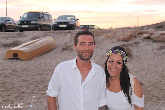 pareja de novios vestidos de blanco en la playa