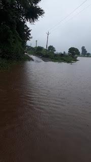 पानी व कीचड़ से लबरेज रपट से निकल रहे ग्रामीण