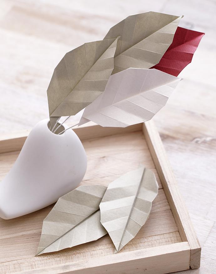 Bunte Origamiblätter in einer kleinen weißen Vase auf Holztablett