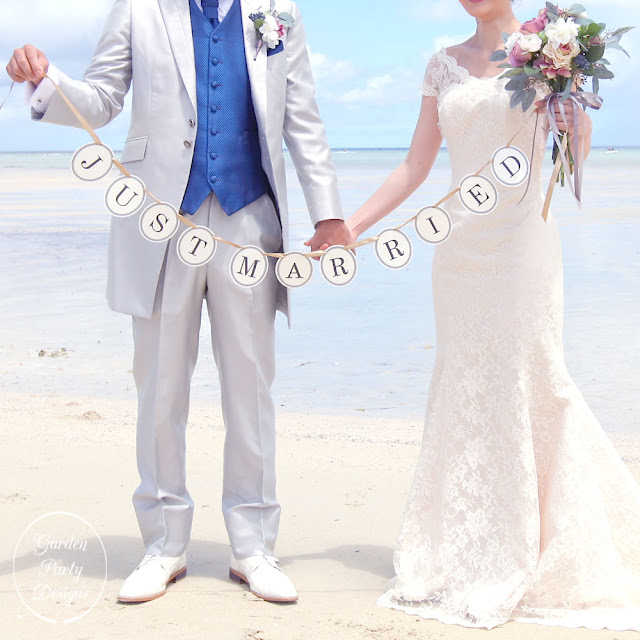 just married ガーランドを持ってビーチで写真撮影