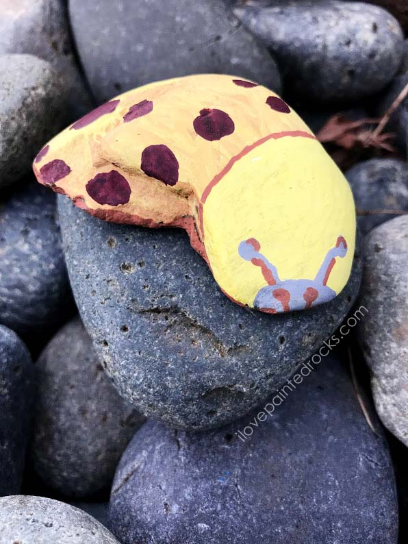 Cool rock painting ideas - a crescent shaped rock painted to look like a banana slug