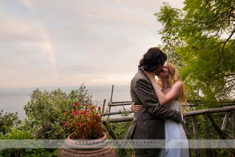 Bride and groom kiss infront of rainbow