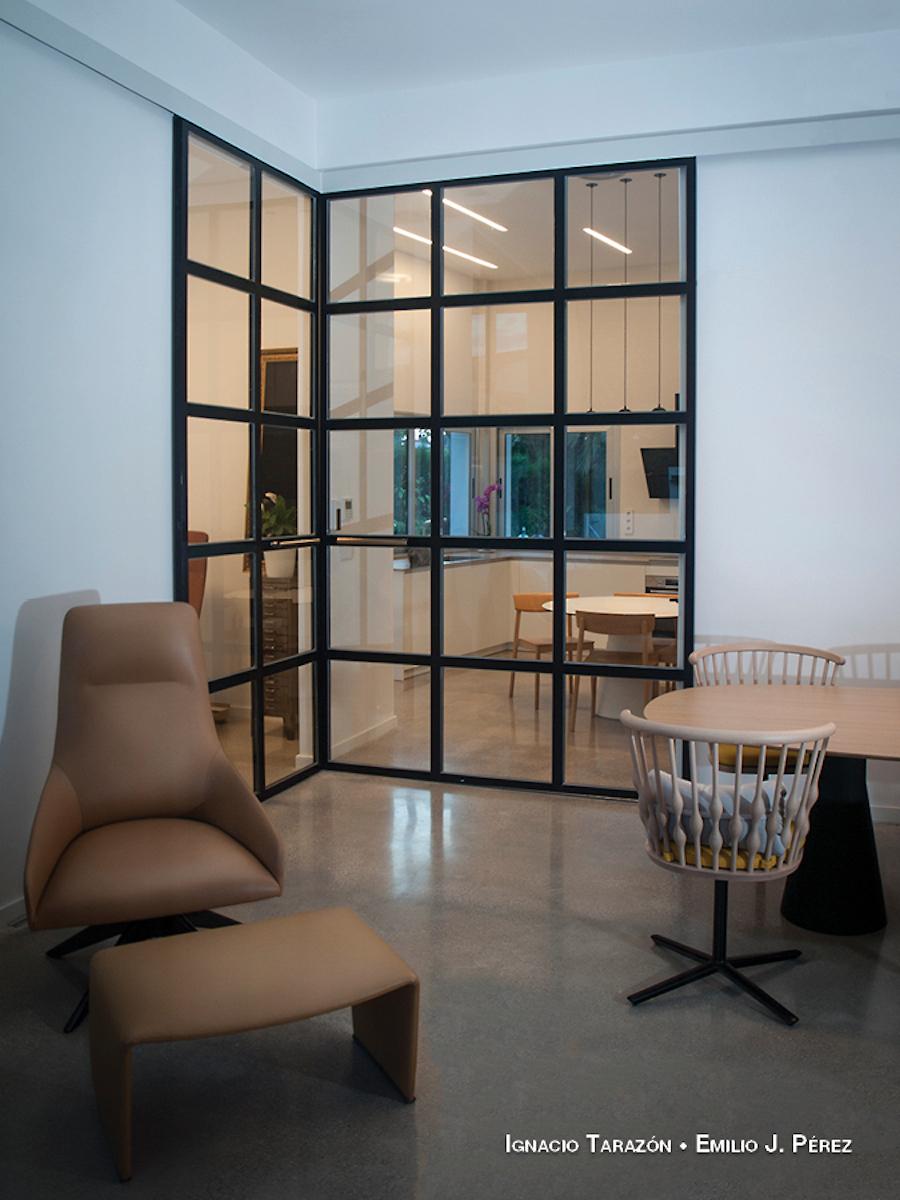 Salón comunicado con la cocina y el despacho con puertas de vidrio y metal