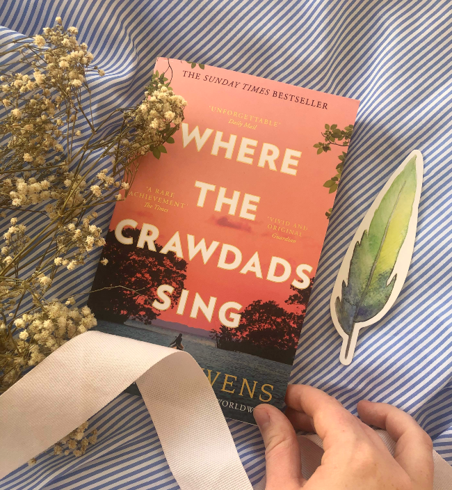 Peach-pink front cover of Where the Crawdads Sing by Delia Owens next to a feather-shaped bookmark
