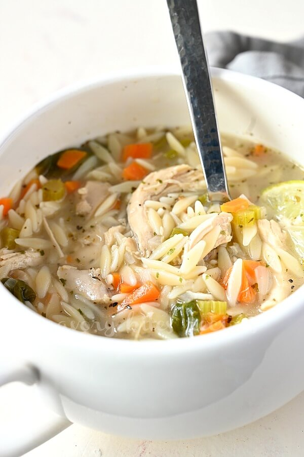 a close up of a white bowl eith lemon chicken orzo soup