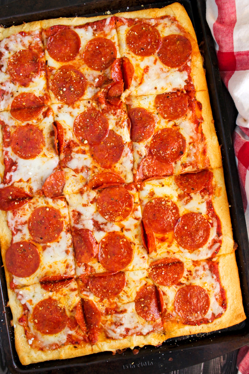 Pepperoni pizza with cresent roll crust on a dark sheetpan.