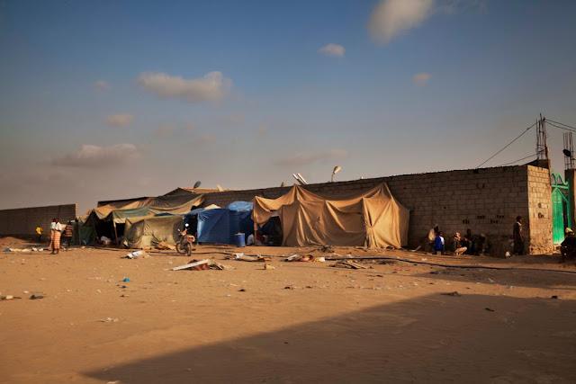 Na imagem aparece um chão de terra batida e algumas tendas improvisadas de lona.