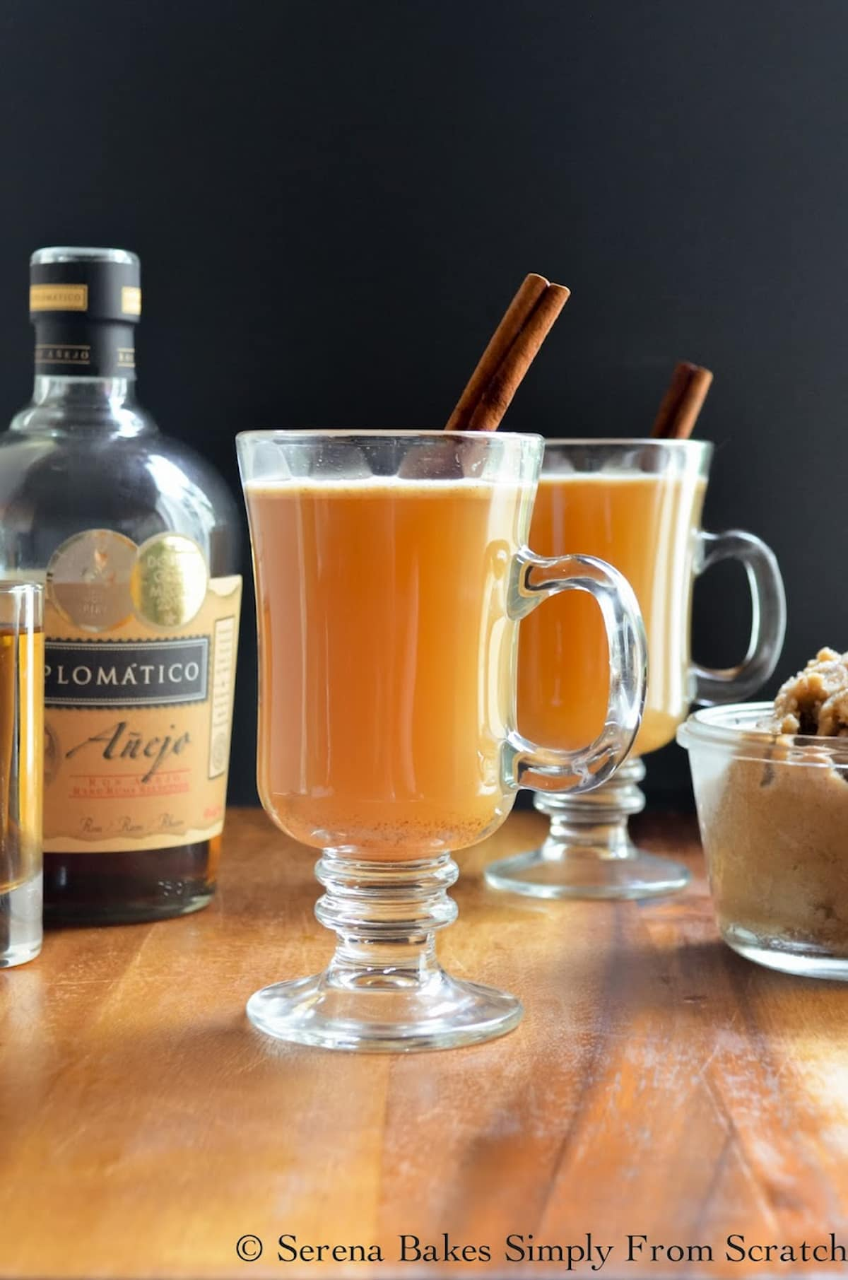 2 glasses of Hot Apple Cider Buttered Rum with a cinnamon stick.