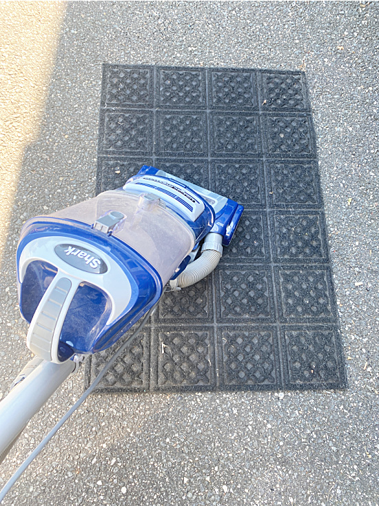 vacuuming the outdoor rug