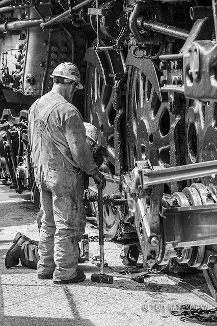 UP 844 steam crew members work on one of the bolts of the locomotive's running gear.