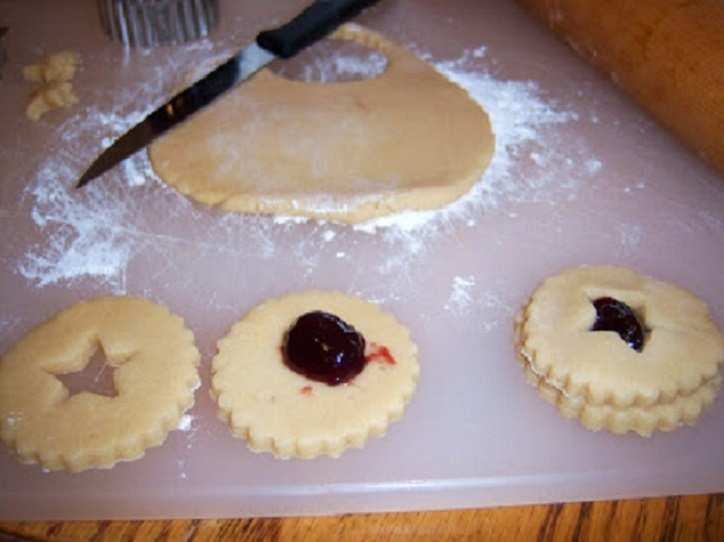 cut out cookies on a cookie sheet ready for baking with raspberry jam filling and a shortbread dough