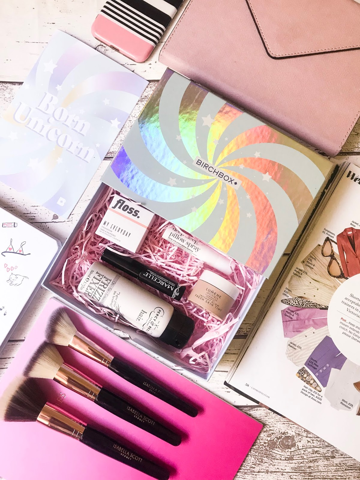 birchbox flatlay with products, notebooks and makeup brushes