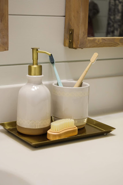 brass toothbrush holder and soap dispenser on a brass tray from hearth and hand