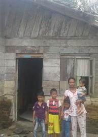Istri Baharuddin dan empat anaknya foto di depan rumah.