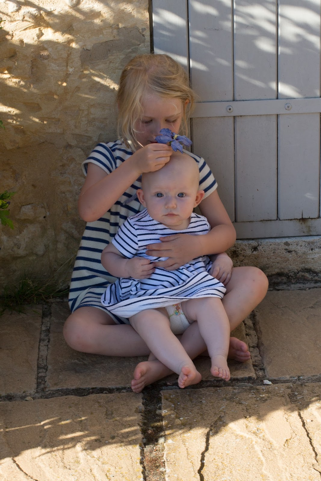 A nearly 5 year old girl and a nearly 6 month old girl sitting on the floor in front of a stone wall. They both wearing white and blue striped dresses and the bigger girl holds a blue flower on the baby's head