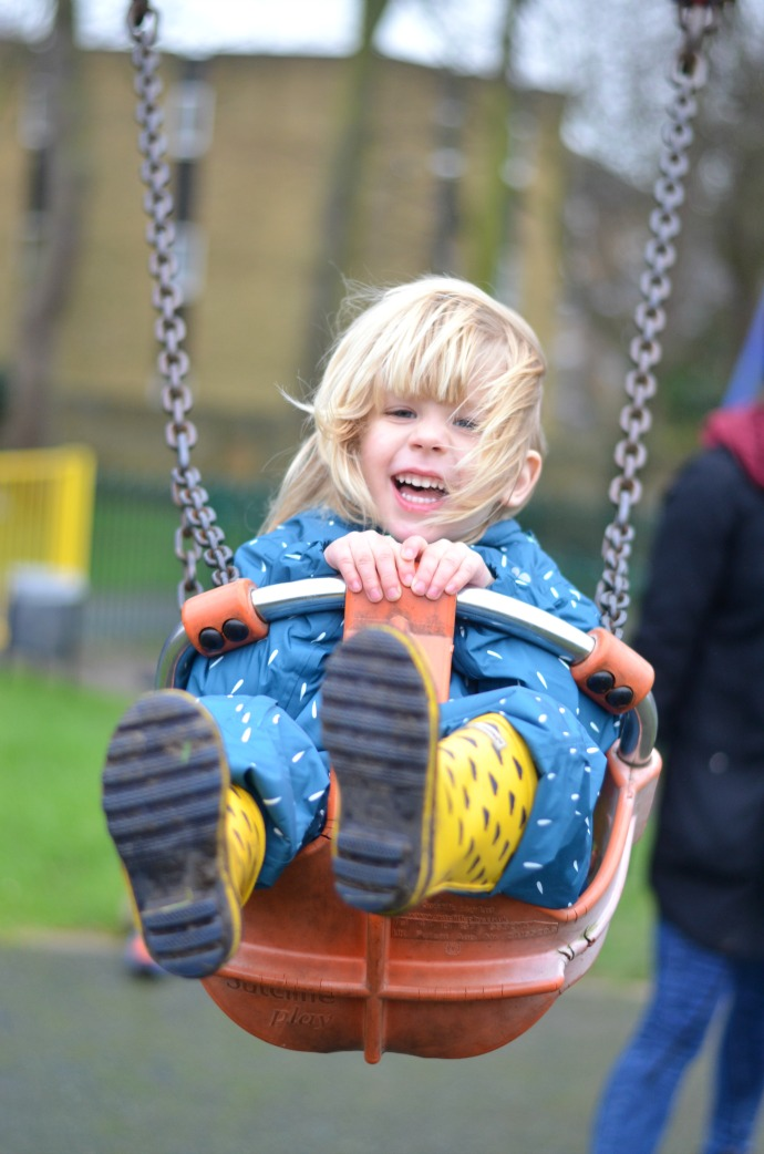 2 year old swinging, muddy puddles, waterproofs for kids
