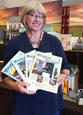 Woman standing in front of a display of one-twelfth scale miniature buildings. She is holding four copies of the Miniature Time Traveller magazine, fanned out.