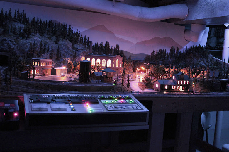 HO scale model railroad layout at night with accessory lighting effects