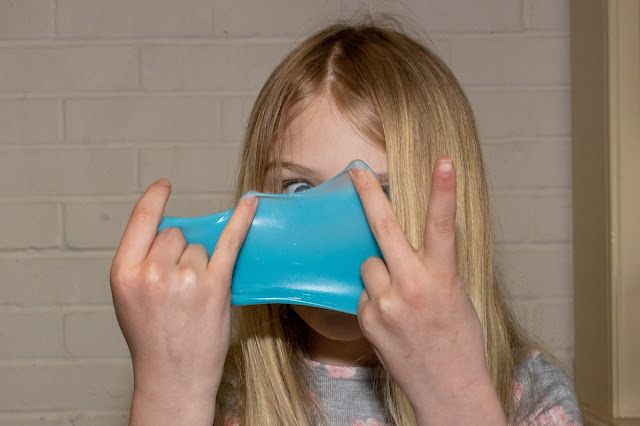 "Blue ""snotty"" slime being stretched in front of a girls face"