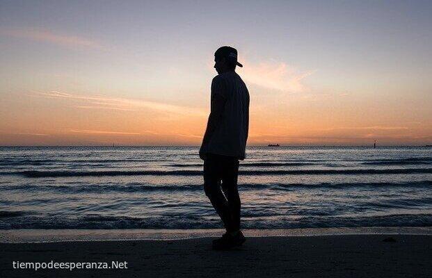 Joven caminando solo por la playa