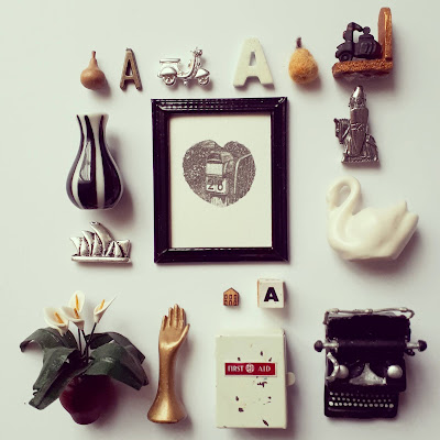 Selection of one-twelfth scale modern miniature accessories arranged around a framed wood engraving. Items include a vintage typewriter, ceramic swan, letter As, wood and felt pears and Vespa ornaments.