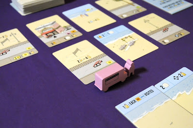 Pink food truck and foodie meeples incentivizing one card on display in Santa Monica boardgame