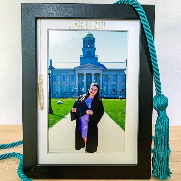 photo of smiling graduate in cap and gown in black frame with white mat decorated with foil transfer gold tassel and Class of 2021 title