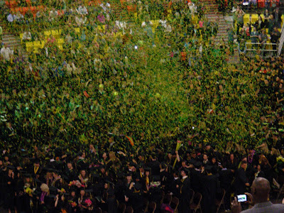 Green and gold confetti fills the air above the graduates at a recent UAA commencement ceremony.