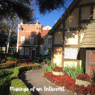 One of the buildings in Epcot UK with a winding side path lined with hedges and flowers