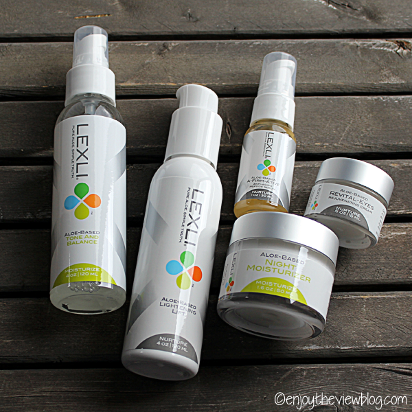 Five different Lexli skincare products lying on a wooden table