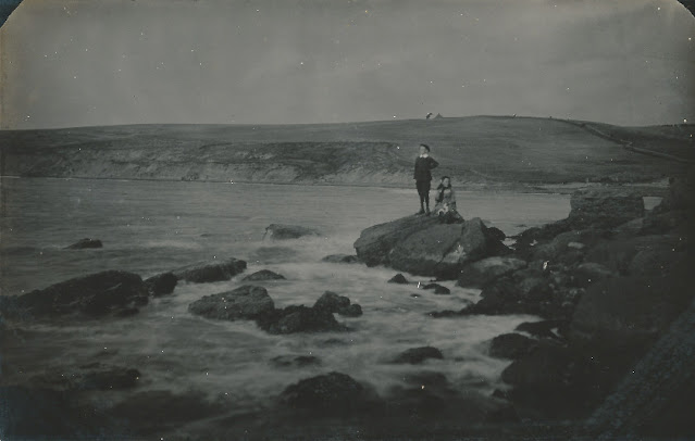 2 children on rock's by the sea