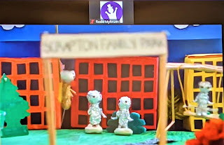 Two tinfoil puppets stand at a public park with buildings in the background.