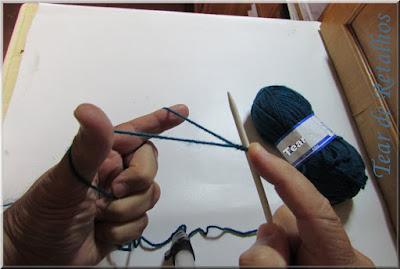 Foto mostrando a posição inicial da montagem à italiana dos pontos de tricô, segurando o nó corrediço e a agulha com a mão direita em posição de estilingue com o fio enrolado na mão esquerda.