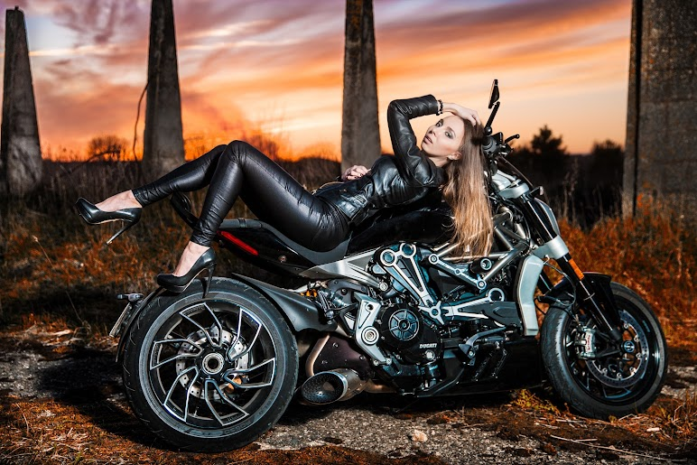 Woman Wearing Black Jacket and Pants Leaning on Touring Motorcycle