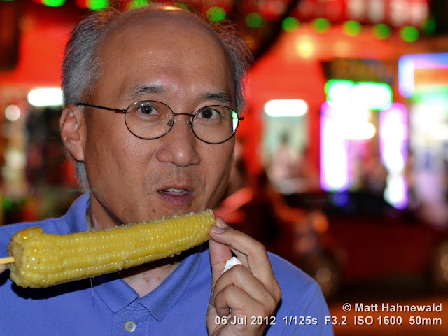 China, Beijing, Donghuamen night market, Chinese food delicacies, portrait, vegetarian Chinese food, Chinese-American man eating corn on the cob