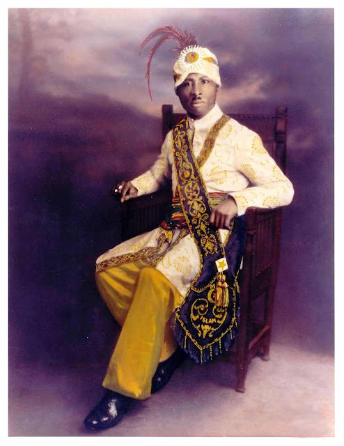 seated portrait of Prophet Noble Drew Ali with turban and feather and regal looking attire