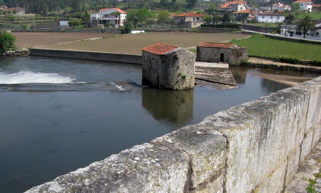 moinhos de água na margem de um rio